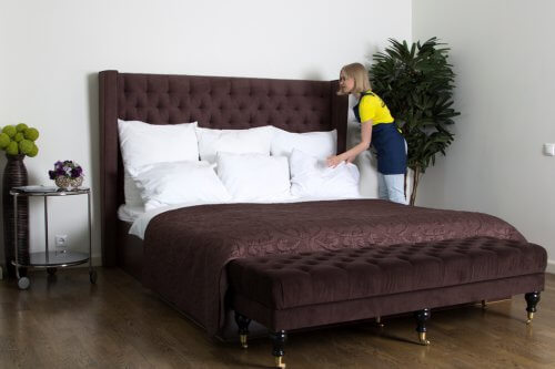 professional cleaner making bed