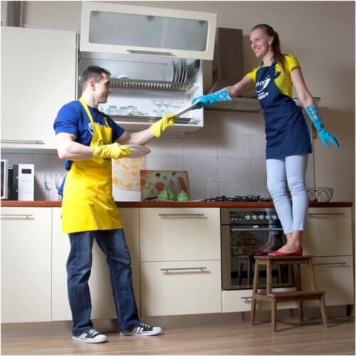 man and woman cleaning kitchen